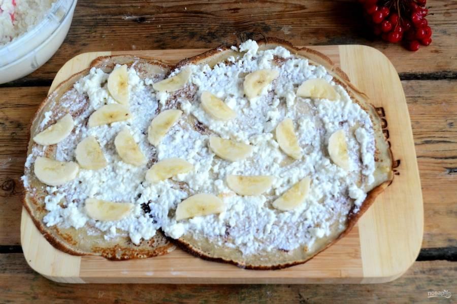 Возьмите 2 блина и положите их на рабочую поверхность внахлест. Смажьте творожной начинкой и разложите небольшие кусочки банана.