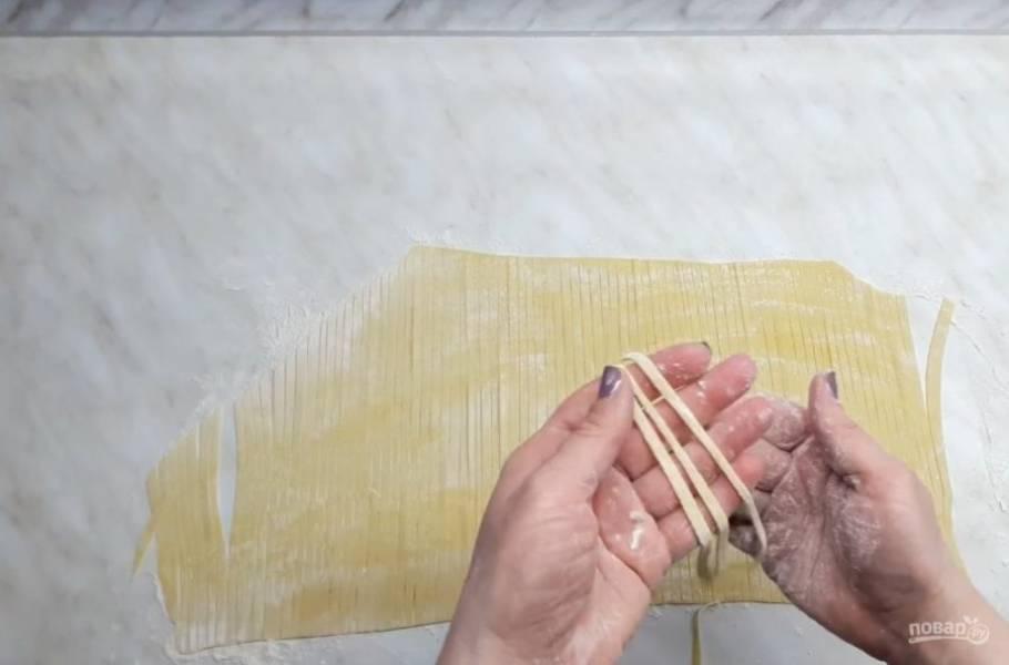 5. Раскатайте тесто в тонкий пласт на присыпанном мукой столе, начиная от середины к краям теста. С помощью ножа для пиццы вырежьте тонкие полоски, это и есть лапша.