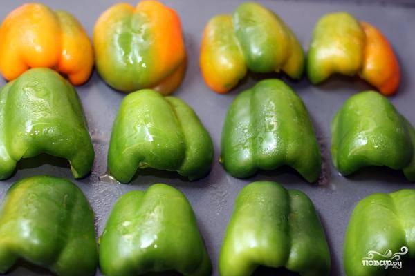 Перцы моем, очищаем от семян и мембран, разрезаем пополам. Выкладываем на противень кожицей вверх, как на фото. Слегка сбрызгиваем оливковым маслом и отправляем в духовку.