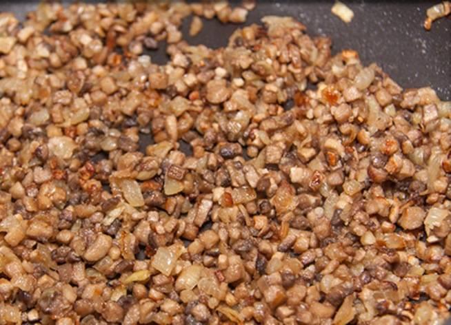 Начинка котлет должна быть холодной, поэтому начнем с неё. Мелко нарежьте лук и грибы и обжарьте на сковороде. Немного посолите и жарьте до испарения влаги.