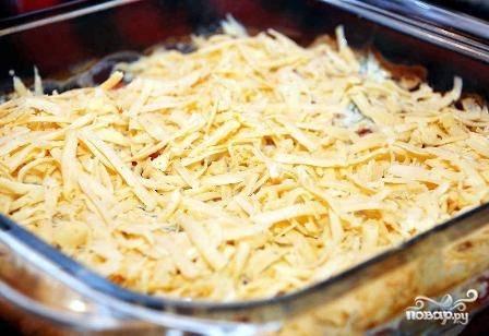 Сыр натираем на средней терке. Достаем форму с рыбой из духовки, посыпаем сыром и ставим обратно.