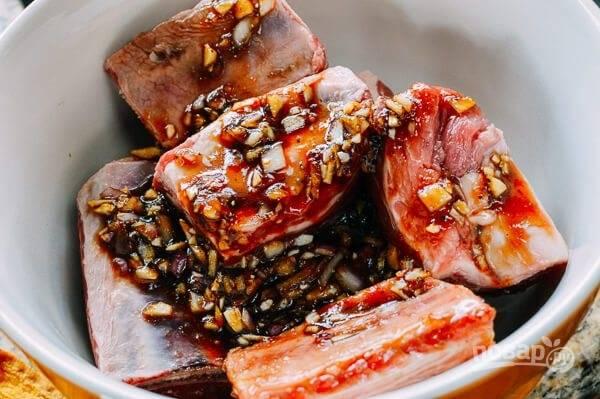 1.Промойте хорошенько ребрышки, оботрите их салфетками и выложите в миску. Добавьте к ребрышкам сахар коричневый, соевый соус, кунжутное масло, 3 измельченных зубчика чеснока, соль, молотый перец. Накройте ребра пленкой и отправьте на 24 часа в холодильник.