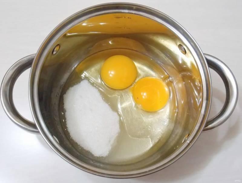 Добавьте к яйцам сахар и маленькую щепотку соли.