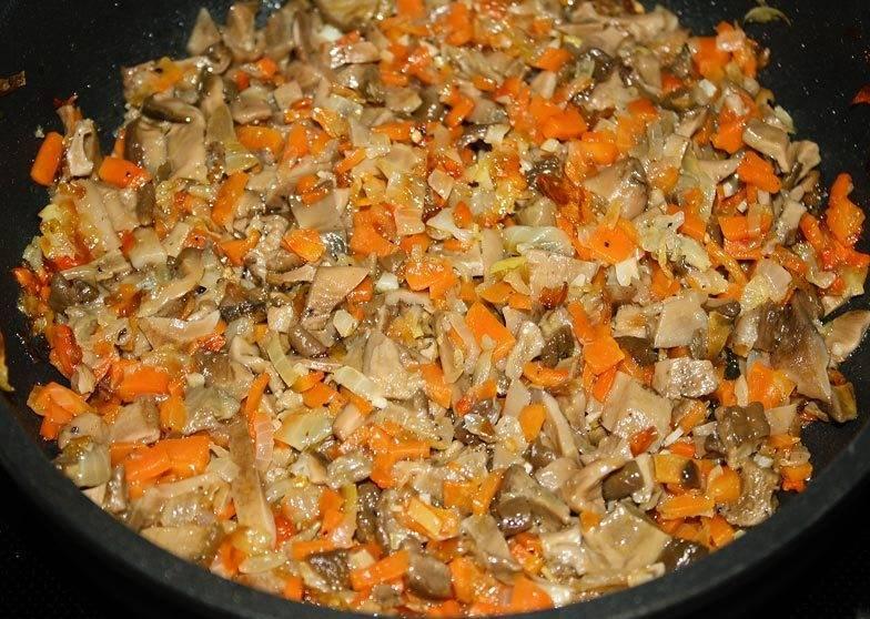 Отваренные грибы нарезаем на небольшие кусочки и выкладываем на сковороду к овощам, перчим все, перемешиваем и жарим 10 минут.
