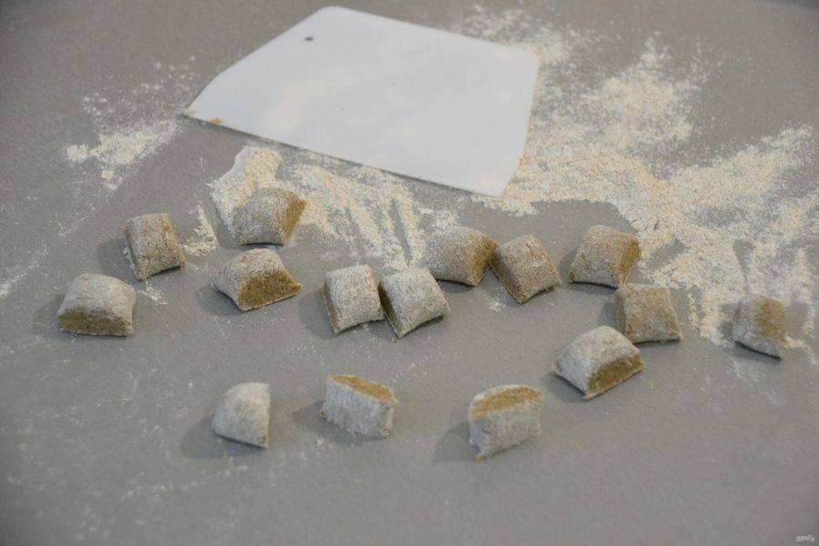 На рабочей поверхности стола, подпыленном мукой, разделайте тесто на колбаски, нарежьте его на небольшие кусочки.