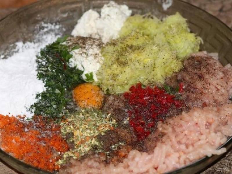 Грудку пропустите через мясорубку. Это же сделайте с морковью и чесноком. К фаршу добавьте творог, кабачок, перец, соль, перец чили, всю зелень, яйцо, крахмал и приправу.