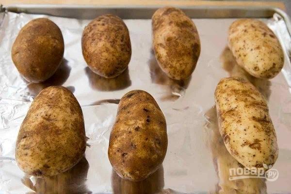 1. Картофель вымойте, обсушите, выложите на противень и отправьте в разогретую до 180 градусов духовку. Запекайте минут 50 до мягкости (время зависит от размера картофеля).