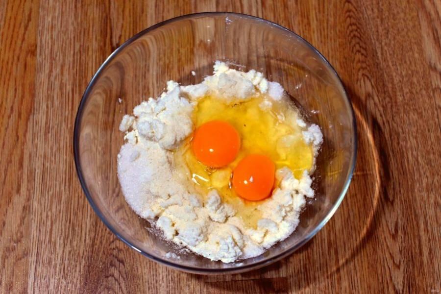 Творог хорошо смешайте с половиной нормы сахара, яйцами и ванилином. Добавьте манку, еще раз перемешайте и дайте постоять 20 минут.