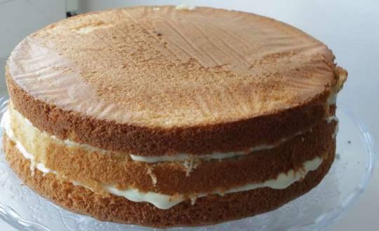 Разрезаем бисквит на три коржа. Каждый корж смазываем кремом и формируем торт.