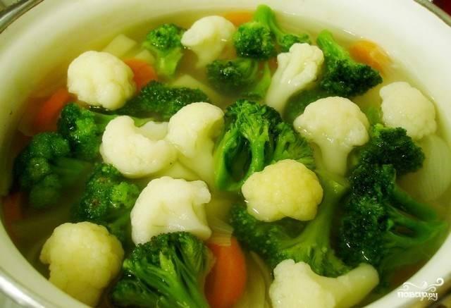 Теперь можно добавлять капусту. Вымойте брокколи и цветную капусту, разберите их на соцветия. Кусочки овощей бросьте в кастрюльку и томите еще пять минут, чтобы капуста не разварилась.