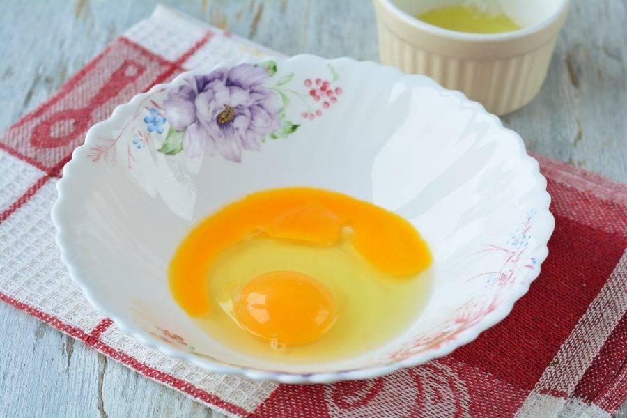 Вбейте в миску 1 куриное яйцо и 1 желток. Белок оставьте для глазури.