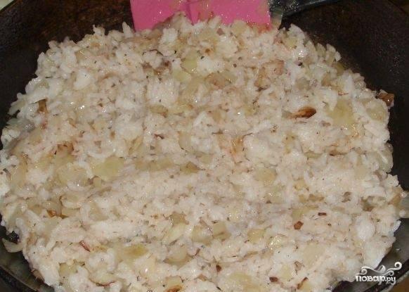 Предварительно отваренный до готовности рис добавляем на сковороду и перемешиваем с обжаренным луком.