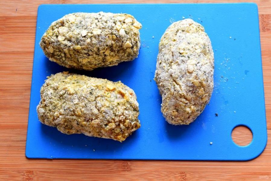 Обваляйте котлеты в муке, затем окуните в яйцо и запанируйте в кукурузных хлопьях. Панировку в хлопьях можно сделать двойной. Уберите котлеты на 10 минут в холодильник, чтобы панировка лучше схватилась.