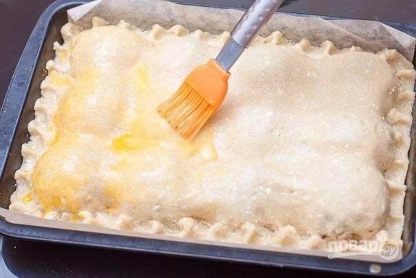 Раскатайте вторую часть теста. Укройте ей пирог, скрепив края. Взбейте желток, и смажьте им верх пирога.