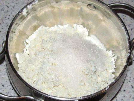 Добавляем в творог половину сахара и перемешиваем.