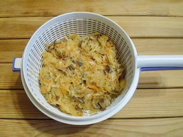 7. Откиньте тушеную капусту с грибами на дуршлаг, чтобы стекла лишняя жидкость.