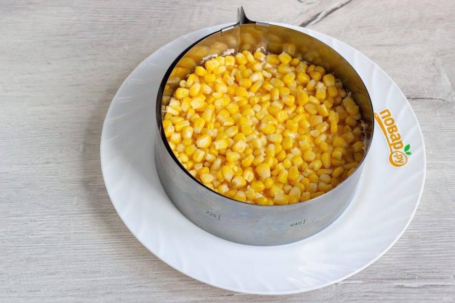Третий слой: кукуруза и заправка. Немного кукурузы отложите для украшения верха салата.