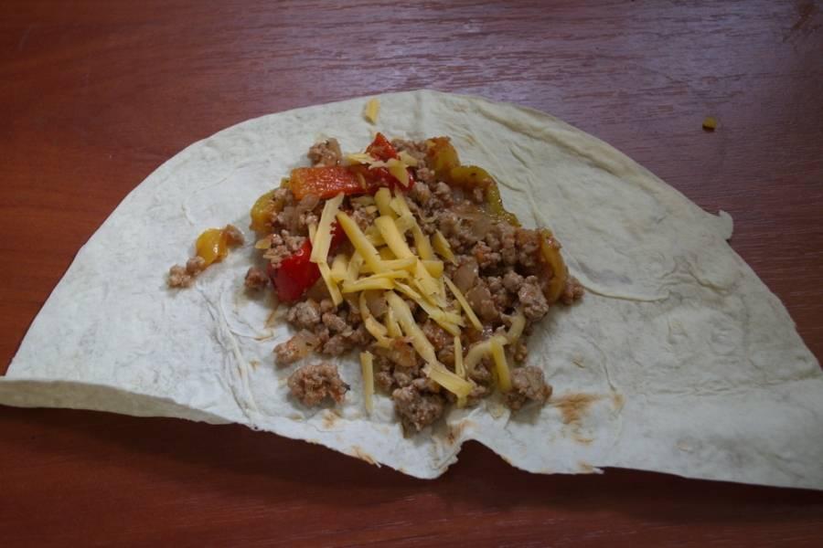 Тушите все вместе до готовности. Можно немного подлить водички. На кусочек лаваша выложите получившуюся начинку. Натрите сыр на терке и выложите поверх начинки.