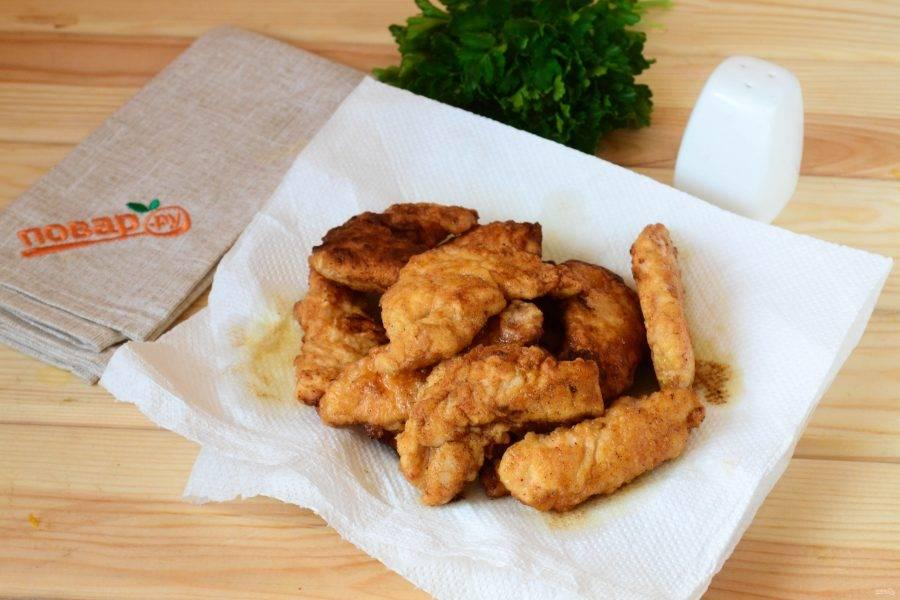 Готовые кусочки курицы во фритюре выложите на бумажные полотенца.