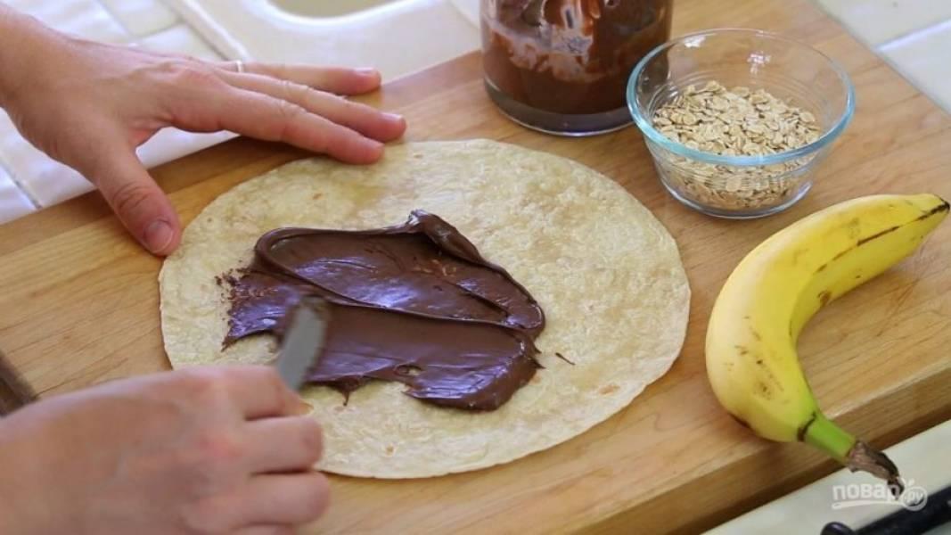 1. Лепёшку выложите на плоскую поверхность. Смажьте её пастой.