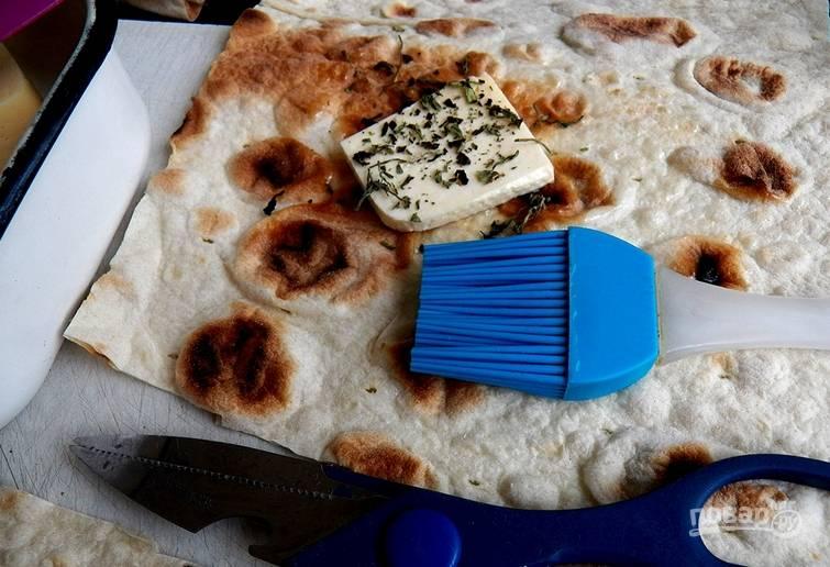Разрезаем оба лаваша на равные части, 6 или 8. Смазываем каждую часть растительным маслом, кладем по одному ломтику сыра, присыпаем сушеным базиликом.