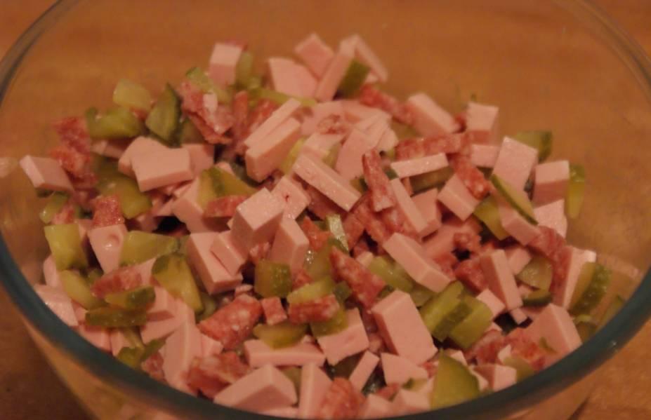 3.Два вида колбасы нарезаем кубиками среднего размера, тоже самое проделываем с огурчиком, все ингредиенты кладем в миску и перемешиваем.