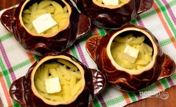 Выкладываем картофель в горшочки, а сверху — кусочек сливочного масла.