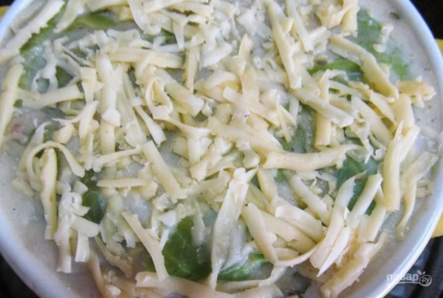 Сверху укройте блюдо капустным листом, а потом — оставшимся соусом. Затем натрите сыр.