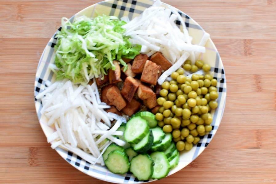 Выложите на красивое блюдо киноа, на него сверху положите кусочки тофу. Вокруг секторами расположите овощи, чередуя их по цвету.