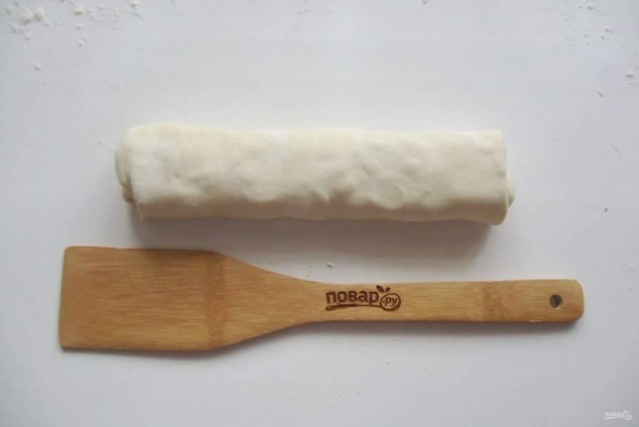 Сверните рулетом тесто с начинкой.
