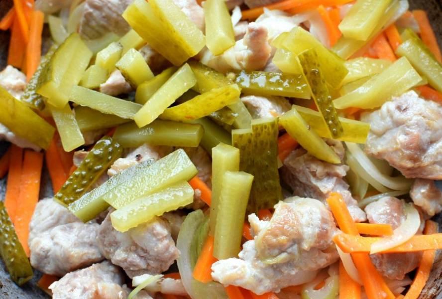 Добавьте лук и жарьте пару минут. Добавьте морковь и маринованные огурцы брусочками, обжаривайте все вместе еще пару минут.