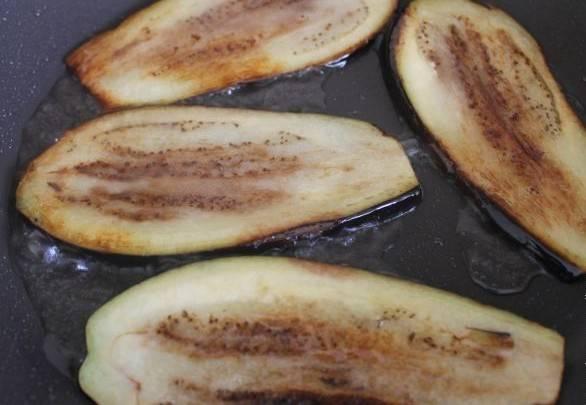 Сливаем воду с баклажанов, подсушиваем их бумажным полотенцем и обжариваем на хорошо разогретом растительном масле в сковороде.