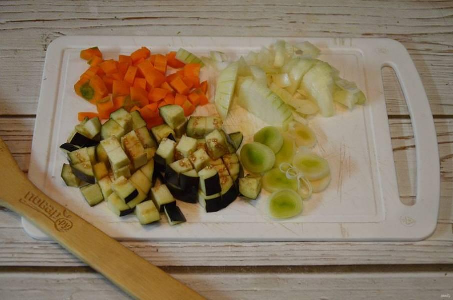 2. Морковь, лук и баклажан нарежьте кубиками, порей - колечками, чеснок порубите.