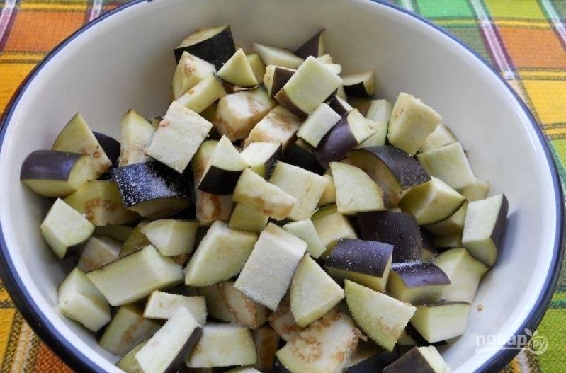 Промытые баклажаны нарежьте кубиками. Засыпьте их солью и оставьте на 30 минут.