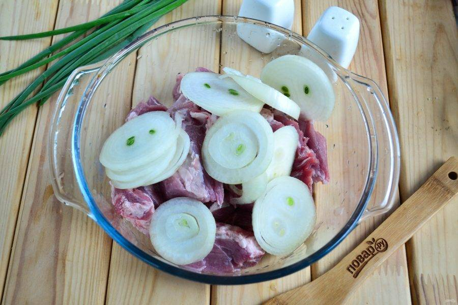 Луковицы порежьте кольцами и отправьте к мясу.