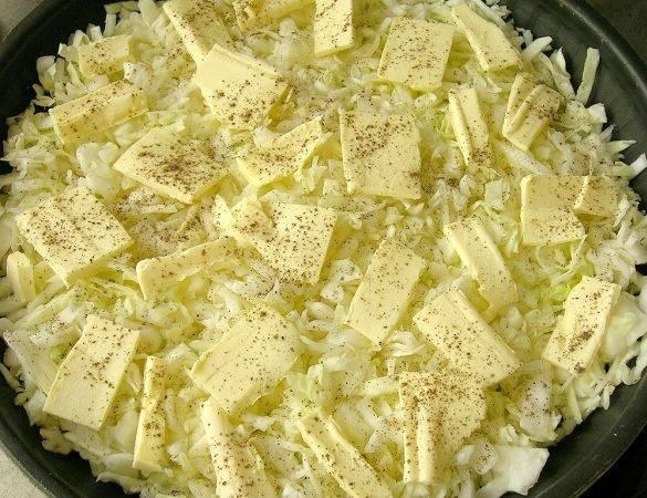 2. Жаропрочную форму с высокими бортами как следует смазать сливочным маслом. Выложить туда капусту ровным слоем. Сверху распределить оставшееся сливочное масло небольшими кусочками.
