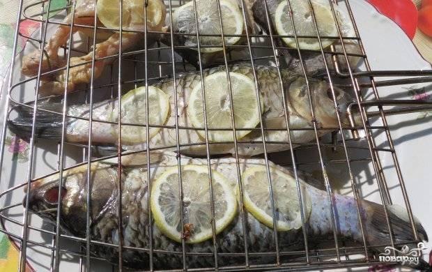 Разогрейте мангал с углями. Решётку смажьте маслом. На неё уложите рыбу. Сверху нарежьте кружками лимон.