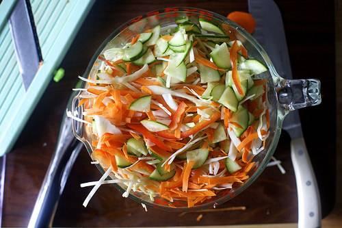 В стерильную трехлитровую банку опустите специи: перец, лавровый лист и семена сельдерея. Капусту нашинкуйте. Нарежьте огурец и морковь тонкими пластинками. Равномерно распределите овощи по банке, так будет вкуснее. Насыпьте сверху соль и сахар.