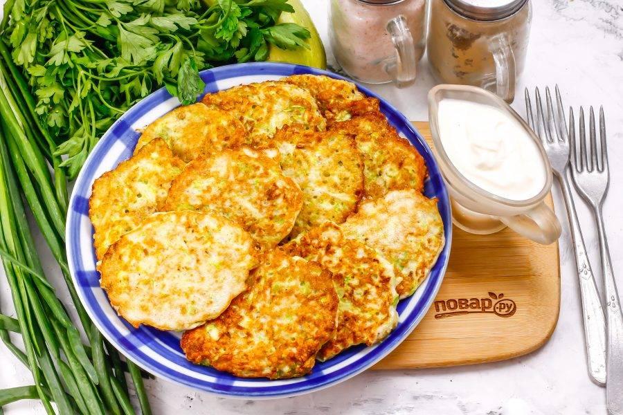 Выложите горячие оладушки на тарелку и подайте к столу со сметаной или греческим йогуртом, чесночным соусом — по вкусу.