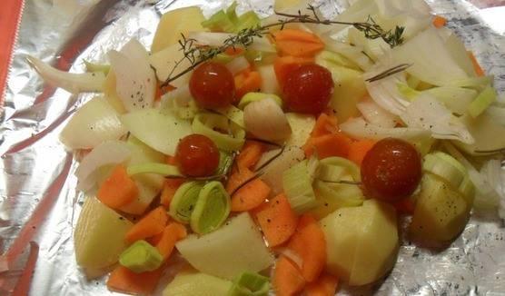 Картофель очищаем и нарезаем кубиками. Солим и перчим все овощи. Помещаем все овощи на разложенный на столе большой лист фольги. Сверху кладем розмарин и тимьян.
