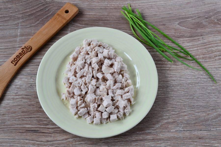 2. Куриную грудку мелко нарежьте и выложите на плоскую тарелку в форме овала. Смажьте небольшим количеством майонеза.