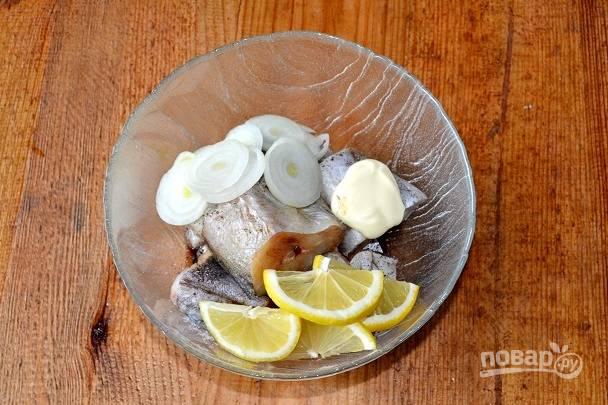 Добавьте нарезанный лук и лимон.