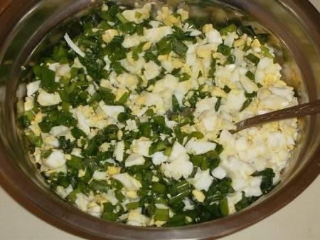 Смешайте яйца и зелень.