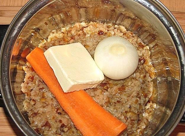 Теперь пропускаем грибы через мясорубку и выкладываем их в кастрюлю. Добавляем к грибам разрезанную надвое морковь, целую луковицу и столовую ложку сливочного масла. Накрываем кастрюлю крышкой и тушим все на медленном огне в течение 40-50 минут, после чего добавляем стакан воды и кипятим все.