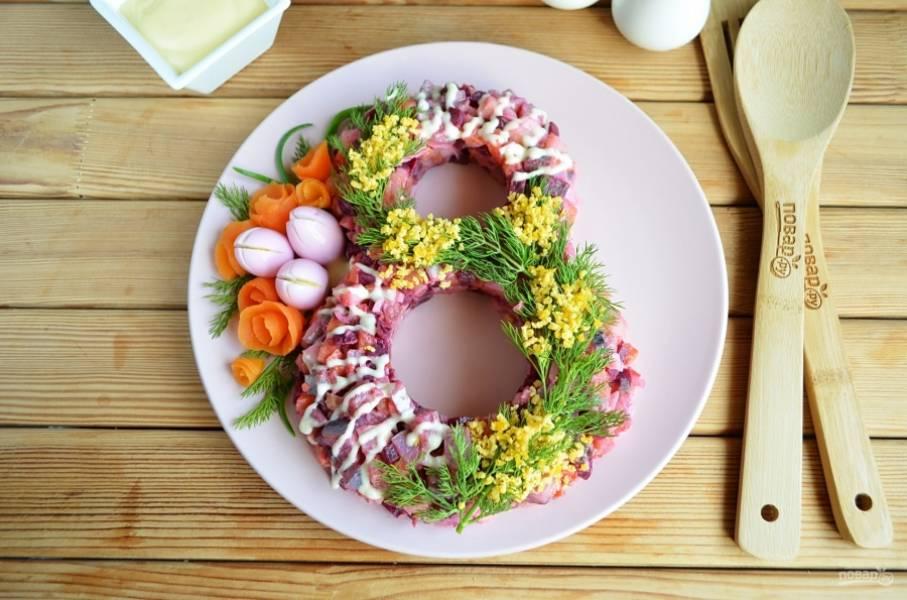 """Из вареной моркови сделайте цветочки, отварите перепелиные яйца, очистите их от скорлупы и опустите на несколько минут в свекольный сок. Сделайте крестообразный надрез на яйцах, чуть придавите пальцами бока, чтобы """"крокусы"""" приоткрылись. Оформите салат веточками укропа, перьями лука. Салат в виде восьмерки готов. Осторожно уберите стаканы. С наступающим!"""