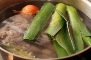 Лук порей порезать, морковь почистить и порезать на половинки, с лука снять верхний слой и воткнуть в него гвоздику.