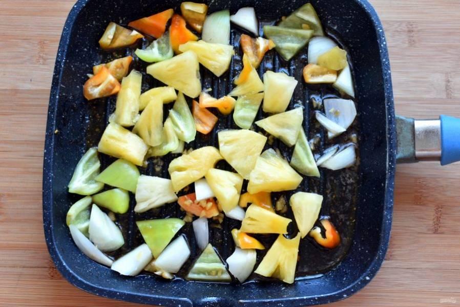 В сковороду выложите нарезанные лепестками лук и перцы, добавьте кусочки ананаса и рубленный имбирь. Обжарьте при помешивании до легкой корочки.