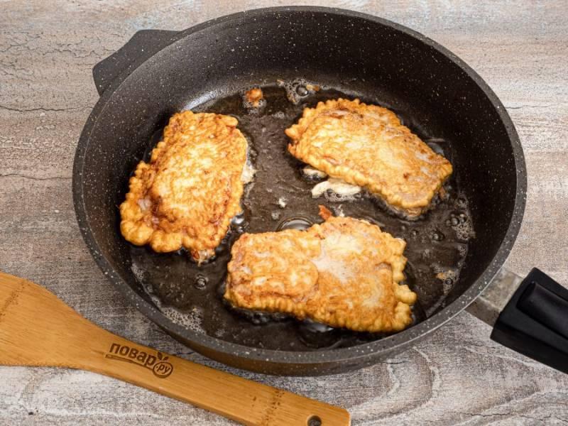 В сковороде разогрейте растительное масло.  Шницель хорошенько окуните в кляр и выложите на сковороду. Обжаривайте на среднем огне с двух сторон до румяности. Затем выложите на бумажного полотенце, чтобы снять излишки жира.