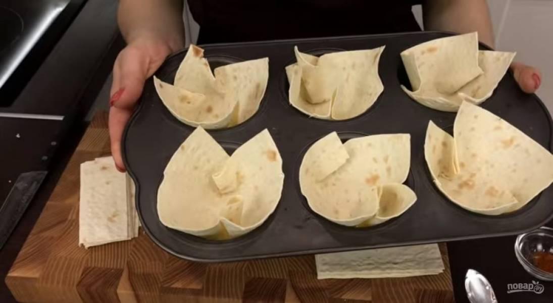 1. Листья лаваша выложите в формочки из-под кексов, придайте им форму чашечки и отправьте в разогретую до 180 градусов духовку, чтобы лаваш засох.