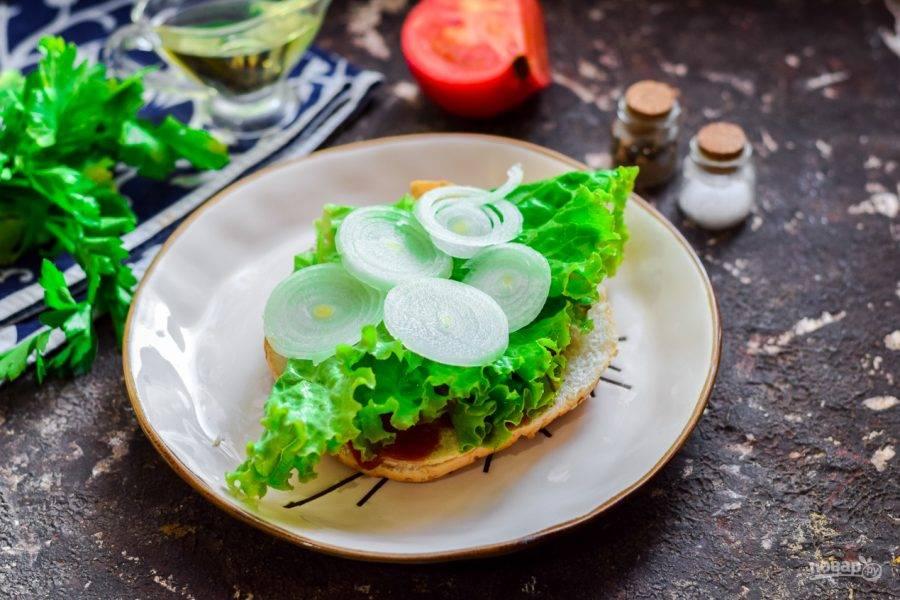 Булку разрежьте пополам, смажьте ложкой кетчупа, уложите лист салата, добавьте кольца лука.